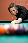 A young man lines up his shot as he breaks the balls for the start of a game of billiards. Shallow depth of field. - Stock Image - C7NJT5
