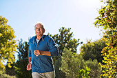 Senior man running in park - Stock Image - DFEKW6