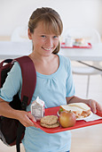 Girl carrying lunch tray in school cafeteria - Stock Image - B4XDB9