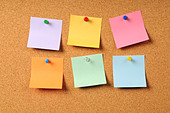 Adhesive notes of various colors pinned to cork surface - Stock Image - BEB886