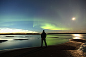 Person standing along the shores of the MacKenzie River with the aurora borealis overhead, Northwest Territories, Canada. - Stock Image - CFC515