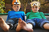 Two Boys Wearing Masks Lying on Trampoline - Stock Image - CX0GCM