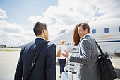 Businessmen talking on tarmac with corporate jet - Stock Image - E3RF5D