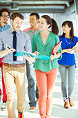 Creative business people with folders walking in office corridor - Stock Image - DXHFX4
