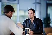 Men having coffee in cafe - Stock Image - DKJ2BA
