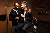 Gay couple drinking wine in kitchen - Stock Image - CTH10Y