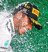 epa04146978 British Formula One driver Lewis Hamilton of Mercedes AMG GP spray champagne on the podium after he won the Malaysian Formula One Grand Prix at the Sepang International Circuit, near Kuala Lumpur, Malaysia, 30 March 2014. British Formula One driver Lewis Hamilton won the race, German Nico Rosberg finished second and German Sebastian Vettel in third place.  EPA/DIEGO AZUBEL - Stock Image - DY0F15