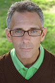 Head and Shoulders Portrait of a Gray Haired Man Wearing Horn Rimmed Eyeglasses a Green Golf Shirt and a Brown V Neck Sweater - Stock Image - B4BEJA