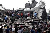 Medan, Indonesia. 30th June, 2015. People gather at the crash site of an Indonesian military plane Hercules C-130 in the capital of North Sumatra province Medan, Indonesia, June 30, 2015. Some 113 people were on board the military plane that crashed into the downtown of Medan, the country's Air Force chief said on Tuesday. © Albert Damanik/Xinhua/Alamy Live News - Stock Image - EWR570