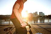 Athletic man riding bicycle on urban bridge at sunset - Stock Image - BJK2HY
