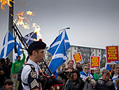 """Craigmillar, Edinburgh, Scotland. Scottish Referendum. 18th Sept.2014. Piper Ryan Rendell from Las Vegas with flames coming from his bagpipes leads the Pro-Independence residents through the streets of Craigmillar, Edinburgh, Scotland on the'Short Walk to Freedom' to the local Polling Station to encourage local residents to vote. Posters for the march read: """"The Pied Piper of Niddrie invites all Yes voters to take part in the march to the short walk to freedom,"""" before adding; """"""""Let's all be Bravehearts!"""" © Arch White/Alamy Live News - Stock Image - E7HE0Y"""