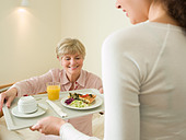 Woman getting lunch served in bed - Stock Image - BJP0WF