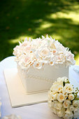 Square wedding cake with a mass of roses - Stock Image - BJKRP8