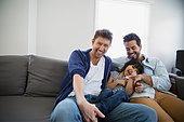Affectionate homosexual couple and daughter on sofa - Stock Image - ERBP8T