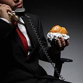 Businessman Having Lunch While on Phone - Stock Image - B0KE0R