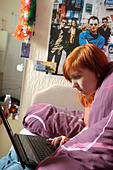 Young Women Laptop Bedroom. - Stock Image - C0A35X