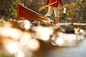 Woman stepping out of canoe in the river - Stock Image - B8BC7M