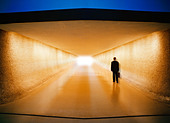 Businessman with briefcase walking down corridor toward baggage claim and ground transportation at an airport - Stock Image - A879F0