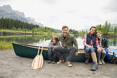 Family sitting by canoe by still lake - Stock Image - E6RD33