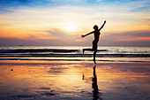 woman silhouette jumping on the beach at sunset - Stock Image - D6RKMM