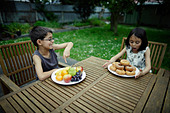 Donuts are good for you. Boy and girl compare healthy platefuls. - Stock Image - BYY2CG