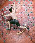 Man climbing indoor rock wall - Stock Image - CT3CT0
