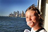 teenage girl looks out over the New York Manhattan skyline USA while blowing her bubblegum.  FULLY MODEL RELEASED/CONSENTED - Stock Image - BX8BKH