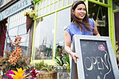 Female florist setting up open sign at flower shop - Stock Image - DA4WK3