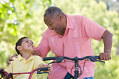 Grandfather and grandson on bikes outdoors smiling - Stock Image - B3K7DW