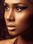 Exotic closeup beauty portrait of a young beautiful woman's face with golden skin and artistic makeup - Stock Image - CMP5FJ