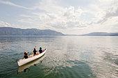 Caucasian children rowing canoe on lake - Stock Image - CF205T