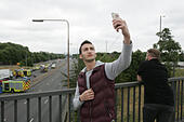 A406 North Circular near Colney Hatch Lane, UK. 13th July, 2015. An onlooker appears to take a selfie at the scene of the crash - some are heard shouting 'is she dead' - the London Fire Brigade, Ambulance Service, London Air Ambulance and Police responded to a serious collision on the A406 North Circular near Colney Hatch Lane in the afternoon of July 13, 2015 © Finn Nocher/Alamy Live News - Stock Image - EXFAGE