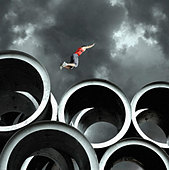 Long jumper on large cylinders - Stock Image - AM395H