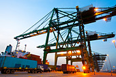Cranes, cargo containers and trucks at a shipping port during dusk - Stock Image - CP3RXW