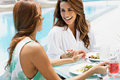 Hispanic women eating lunch poolside - Stock Image - BEA7FN