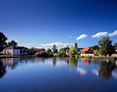 View across one of several large ponds towards the picturesque village of Great Massingham. - Stock Image - CF438X