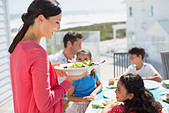 Family eating lunch at table on sunny patio - Stock Image - DRCKDC