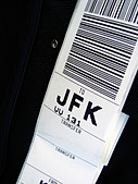 Closeup of a Luggage Tag enroute to John F Kennedy Airport in New York City Copy Space - Stock Image - APBJG8