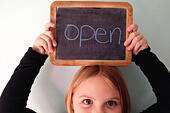 Girl (6-7) holding open sign above her head - Stock Image - E8FR41