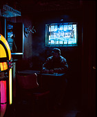 man drinking, interior of bar, lit daylight and neon, - Stock Image - BT2R2M