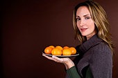 A mid adult woman holding a plate of clementines - Stock Image - BH6AN1