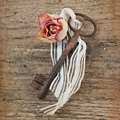 old rusty key with flower on a wooden background - Stock Image - CWKN3T
