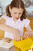 Girl packing up a packed lunch - Stock Image - BD52F4