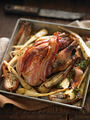 Bacon-wrapped pheasant and vegetables - Stock Image - BJKG2P