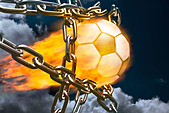 Burning soccer ball breaking through chains - Stock Image - BE66M6