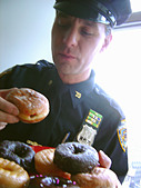 Portrait of a New York City Police Officer Near a Window He is About to Eat a Jelly Donut - Stock Image - AT6AWM