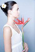 young woman with bird of paradise flower - Stock Image - AM4WN5