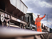 Railway workers signaling train - Stock Image - CYKXGP