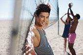 Man leaning on beach volleyball net - Stock Image - CNMHBJ