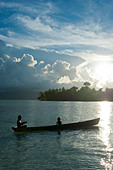 Boys in a canoe in backlit in the Marovo Lagoon, Solomon Islands, Pacific - Stock Image - D1G26B